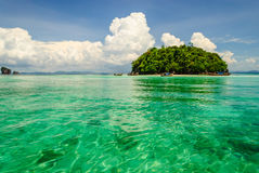 海岛在透明海的绿色水中 免版税库存照片
