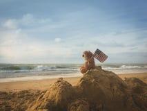 海岸、天际、沙子山和玩具熊与旗子 免版税库存图片