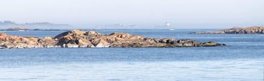 海岸、峭壁和一个遥远的烽火台围拢与雾晴天 免版税库存图片