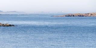 海岸、峭壁和一个遥远的烽火台围拢与雾晴天 图库摄影