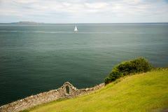 海岸、草覆盖的小山边和老石墙有户外窗口的,爱尔兰 免版税库存图片