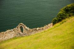 海岸、草覆盖的小山边和老石墙有户外窗口的,爱尔兰 免版税库存照片