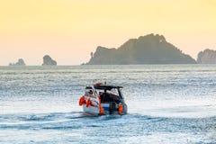 海岸卫队从岸的汽艇风帆 日落天空和山在背景中 人驾驶救生员船 库存照片