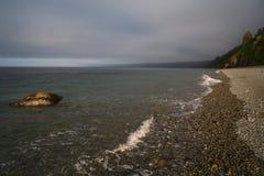 海岸和一块石头在水中 库存照片