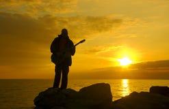 海岸孤独夜间的吉他弹奏者 免版税库存图片
