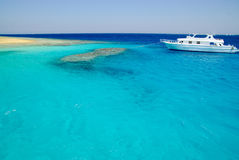 海岸珊瑚附近的礁石沙子游艇 库存照片
