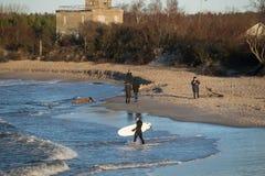 海岸的冲浪者在冬天 免版税库存图片