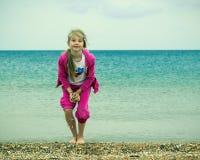 海岸的女孩,准备投掷极少数壳 免版税库存照片