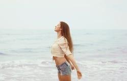 海岸的少妇享用新鲜空气的 免版税库存图片