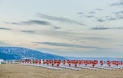 黑海岸的看法 与房子、蓝色海水、云彩日落天空、海滩沙子与伞和sunbeds的青山 库存图片