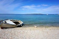 海岸的美丽的Pebble海滩与蓝色海和天空和老下沉的小船钓鱼的 库存图片