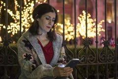 海岸线圣诞节看电话的生活方式妇女 免版税图库摄影