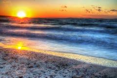 海岸线在黄昏的五颜六色的天空下 库存图片