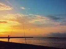 海岸线的孤独的渔夫 渔夫SunriSilhouette反对剧烈的天空的 库存照片