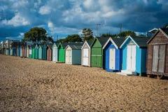 2016年海岸美丽的宽海滩的英国Mersea五颜六色的房子与有趣的大厦 库存图片