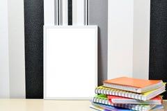 海报模板的框架嘲笑与在木桌上的色的笔记本 库存图片