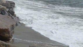 海挥动移动在与岩石的含沙海岸上生产轻的泡沫似的浪端的白色泡沫 股票录像