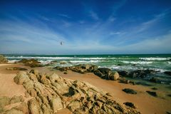 海挥动鞭子线在海滩的冲击石头 与sandand秀丽的岩石海岸线 库存图片