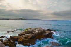 海挥动飞溅在岩石在沿海线与城市在 免版税库存照片