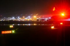 海斯罗机场反射湿表面的柏油碎石地面在与英国航空公司平面准备的多雨夜为起飞和光- 免版税库存图片