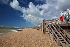 海斯廷斯,英国- 2017年7月23日:在2016年与码头的五颜六色的海滩对公众重建了并且打开在背景和蓝色s中 库存图片