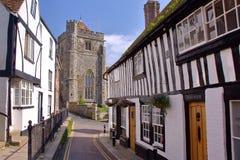 海斯廷斯,英国- 2011年7月31日:有圣Clement教会的16世纪用木材建造被构筑的和中世纪房子在背景中 免版税库存照片