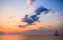 海日落和一条sailling的小船 库存照片