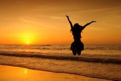 海日落的愉快的跃迁妇女在krabi泰国 免版税图库摄影