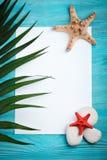 海星、海说谎在蓝色木背景的石头、棕榈叶和壳 有标签的一个地方 免版税图库摄影