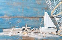 海星和壳与玩具小船和蓝色木背景 库存图片