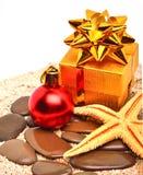 海星,圣诞节中看不中用的物品,在沙子的礼物盒 免版税库存图片