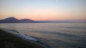 海是镇静的在日落,并且月亮在天空发光 图库摄影