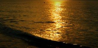 海晚上阳光反射的表面是金黄的 免版税库存照片