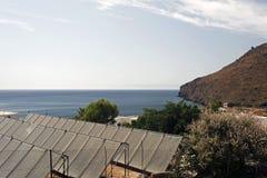 海景、山和太阳电池板的看法在一个房子的屋顶在希腊海岛,拔摩岛在夏天 免版税库存照片