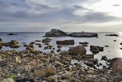 海景、石头和冰砾在日落前 库存图片