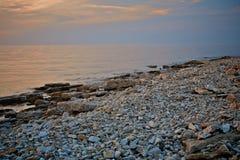 海景视图 多岩石的海滩在晚上 小卵石岸 全景 库存照片