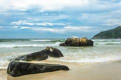 海景:由海边的巨大的石头与水飞溅 库存图片