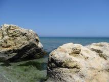 海景-两个岩石在前景、绿松石海表面和清楚的天空的水中没有在天际上的云彩 免版税库存照片