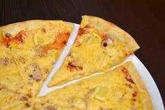 海比萨用乳酪、柠檬、金枪鱼和乌贼在一块白色板材在一张黑暗的木桌上,被切除的一件 库存图片