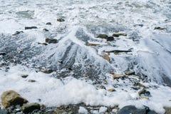 海波浪从石岸滚动下来,留下泡沫在海滩 免版税库存照片