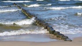 ?? 海波浪击中了与木防堤的岸 免版税库存照片