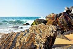 海波浪和岩石在海滩在马尔格拉特德马尔,西班牙 免版税库存图片