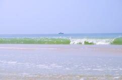 海波浪和渔夫的小船 库存照片