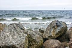 海波浪在一块大石头划分 库存照片
