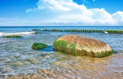 海波浪在一块大石头划分 库存图片