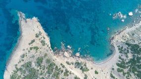海波浪空中顶视图击中在海滩的岩石与绿松石海水 免版税库存照片