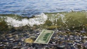 海波浪给金钱。 免版税库存照片