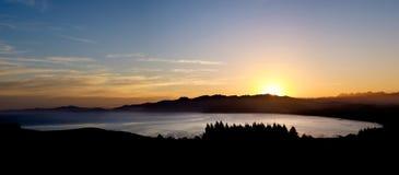 海洋、山、树和五颜六色的天空全景  库存照片