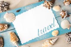 海洋夏天明信片 在蓝色木板的贝壳在海滩的沙子 库存图片