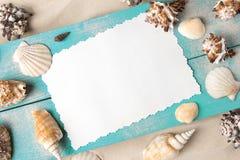 海洋夏天明信片 在蓝色木板的贝壳在海滩的沙子 免版税库存照片